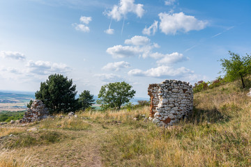 Ruin of the chapel and stone wall on meadow, with trees and grass. Summer weather with blue sky
