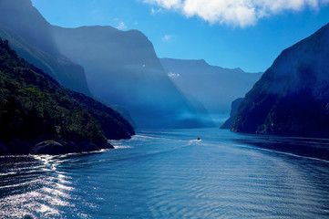 Small boat sailing in early morning mist in Milford Sound, New Zealand