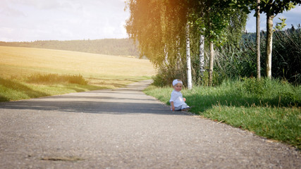 the child is sitting on the road