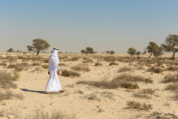 Arab man in national dress in the desert of Dubai
