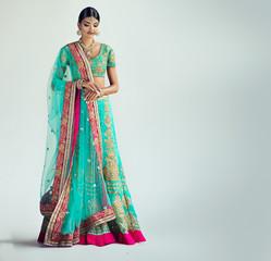 Portrait of beautiful indian girl. Young hindu woman model with kundan jewelry set. Traditional Indian costume lehenga choli or sari
