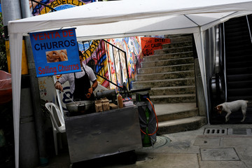 """Man sells sweet fritters (churros) next to a public outdoor escalator in the """"Comuna 13"""" neighborhood in Medellin"""