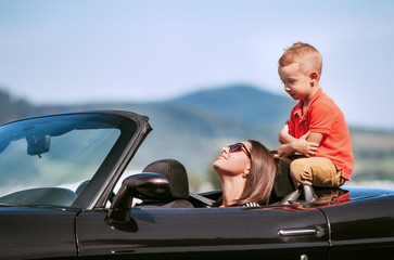 Mother with little son sit in cabriolet car