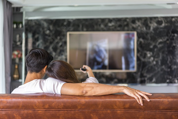 Relaxed young couple watching tv at home.