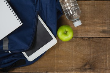 Schoolbag, apple, water bottle, book and digital table on wooden