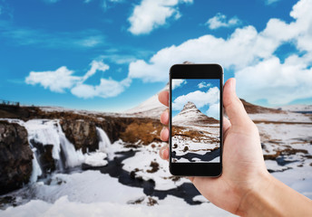 Taking landscape of mountain Kirkjufell in winter by mobile smart phone