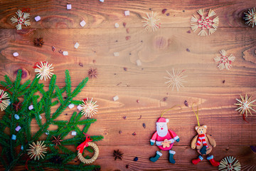 Christmas background with straw decorations, spices, marshmallow on old rustic wooden board, top view, copy space
