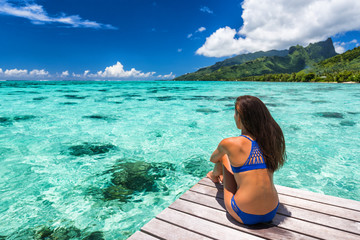 Wall Mural - Travel vacation bikini woman at luxury resort overwater villa in Tahiti. Cruise ship destination, exotica holiday island. Girl from behind relaxing sunbathing looking at ocean, tanned body.