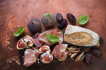 Above view of bruschettas with prosciutto ham, ripe figs and date fruits on a rusty metal background