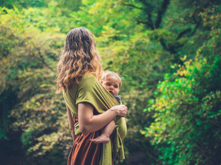 Mother with baby in sling in nature