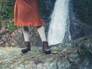 Feet and legs of woman by waterfall