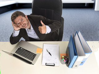 attractive businessman  happy and confident at office with paperwork file working on laptop computer
