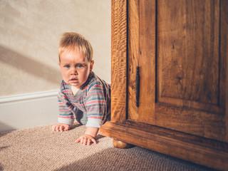 Little baby hiding behind wardrobe