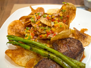 Steak Filet With Chips Salsa Asparagus on White Plate in Chilean Restaurant