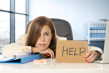 attractive sad and desperate business woman suffering stress at office laptop computer desk holding help sign
