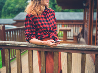 Young woman with phone on porch of cabin