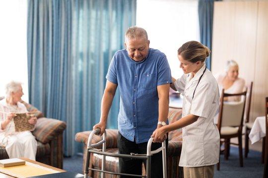 Female doctor assisting senior man walking with walker