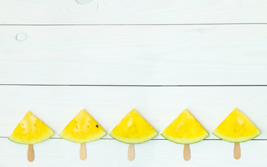 Yellow watermelon slices on sticks