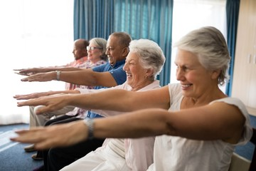 Cheerful senior people exercising with arms raised