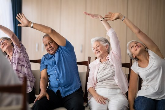 Senior people stretching while sitting on chairs