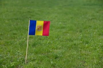 Andorra flag on a green grass lawn field background. National flag of  Andorra waving outdoors
