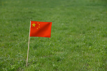 China flag, Chinese flag on a green grass lawn field background. National flag of the People's Republic of China waving outdoor