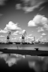 Harbor of Kotka large cranes are reflected in the sea under the cloudy sky