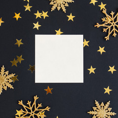 Mock up greeteng card on black background with Christmas decorations glitter snowflakes and gold stars confetti. Invitation, paper. Place for text flat lay