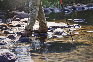 Waterproof hiking boots wade a rocky mountain stream. The concept of high quality outdoor equipment