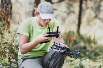 closeup on male hands of drone operator with an amateur quadcopter remote control joystick, outdoors