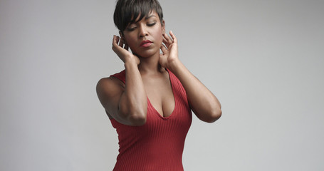 Sensual seductive dancing hot African latina woman in tight fitting ribbed sleeveless dress isolated