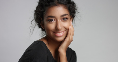 young girl with perfect light brown skin and beautiful curly black hair smiling at the camera in studio