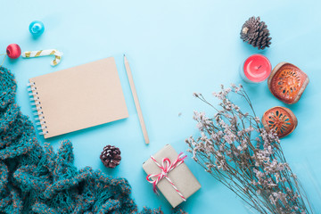 Flat lay of blank craft notebook, Christmas ornaments and gift boxes on pastel color background