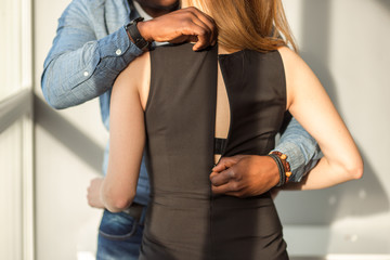 Handsome fashion african man undressing woman . Seduction and passion.