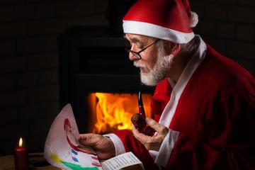 Weihnachtsmann schaut selbstgemaltes Kinderbild an