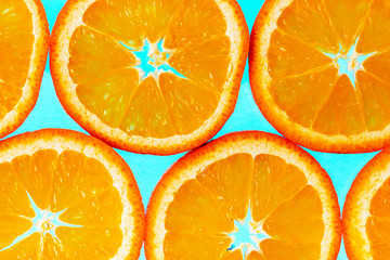 Abstract background with citrus-fruit of orange slices. Light blue background. Close-up. Studio photography.