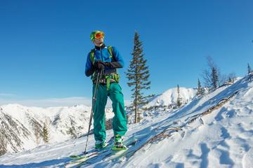 Man skier freerider standing at top of ridge, adventure winter freeride extreme sport