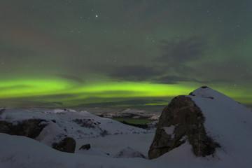 Winter, night, frozen lake and aurora borealis above the hills .