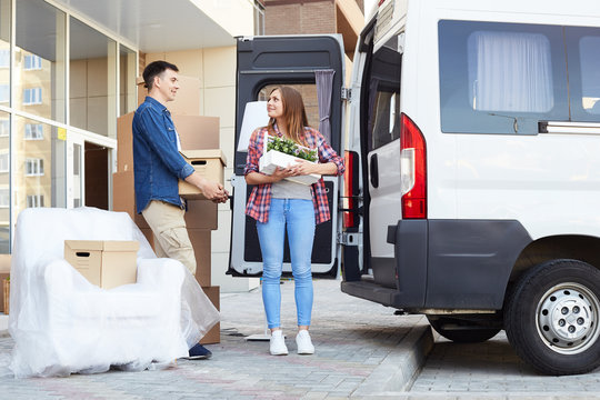 Portrait of happy  young couple embracing and smiling while loading cardboard boxes to moving van outdoors