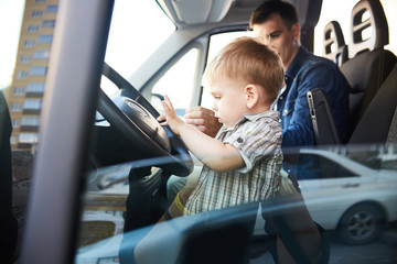 Portrait of cute little kid pressing the horn button on wheel sitting on front seat of car with dad