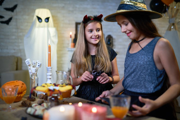 Portrait of two teenage girls wearing witch costumes setting up snack table at Halloween party in decorated room