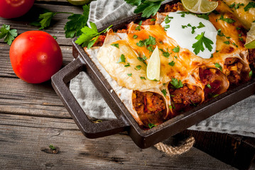 Mexican food. Cuisine of South America. Traditional dish of spicy beef enchiladas with corn, beans, tomato. On a baking tray, on old rustic wooden background. Copy space