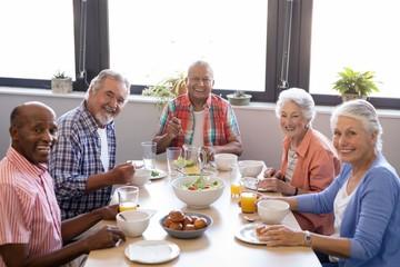 Portrait of senior people having breakfast at table