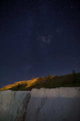 Night starry sky over the quarry for the extraction of chalk.