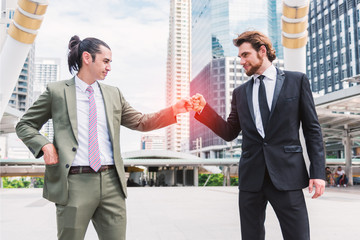 Fist bump or Knuckle bump between two businessmen agreement at outdoor in the city, Business cooperation and participation concept, power of teamwork or teammate