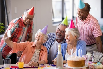 Smiling senior people taking selfie at party