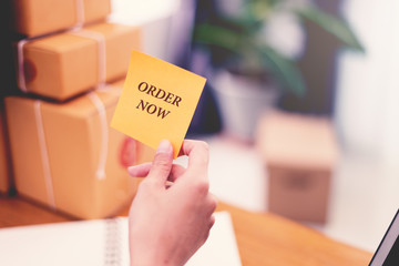 """""""Order Now"""" text on post it paper in woman hand at post office with many boxes, Online shopping and Marketing concept idea. Split and cross processing tone pinterest and instragram like process."""