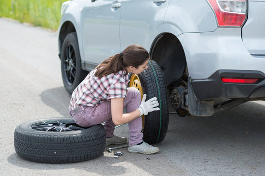 Young european woman changing car tire on rural road