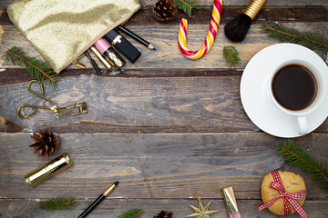Cosmetics for make-up and Christmas decorations on a wooden background. Flat lay