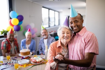 Portrait of senior couple wearing party hats standing by table
